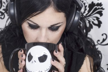 Beautiful gothic girl listening to music and holding a cup of coffee or tea