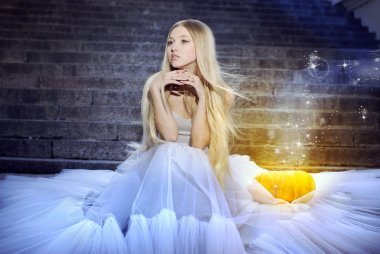 Beautiful girl dressed as Cinderella is sitting on the steps