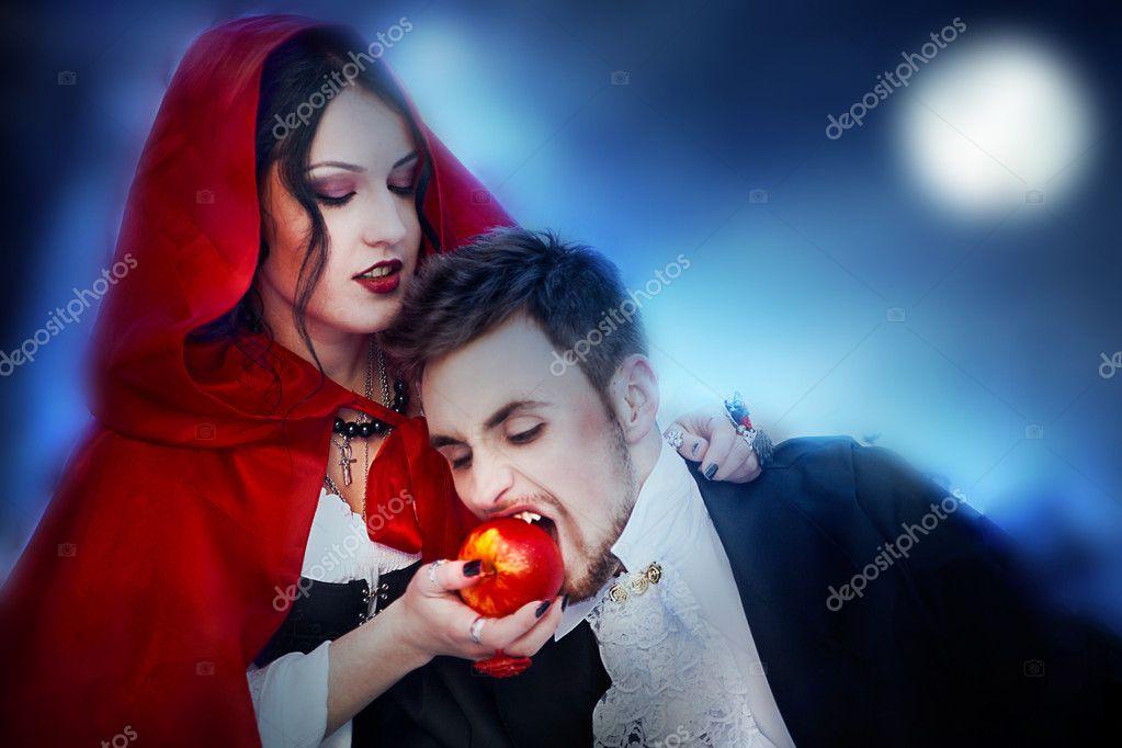 Beautiful girl by night vampire feeds an apple