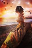 Fényképek Gyönyörű lány ül egy sziklán, napnyugtakor a tenger figyelte