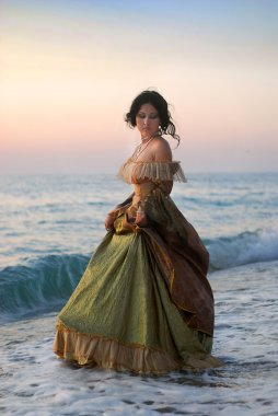 A beautiful young girl in a vintage dress is in the sea