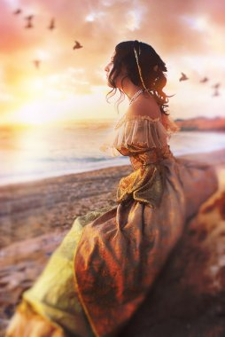 Beautiful girl sits on a cliff at sunset watching the sea