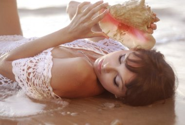 Beautiful girl lying in the sea and the hands holding seashell