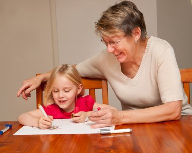 A little girl drawing with her carer