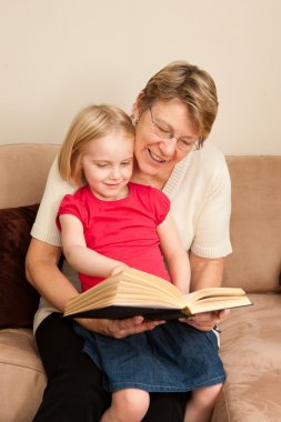A grandmother or Nanny reading to a 4 year old little girl