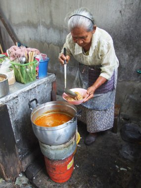 Bangkok October 2010.The old woman drew a plate of food to customers at market , Bangkok thailand