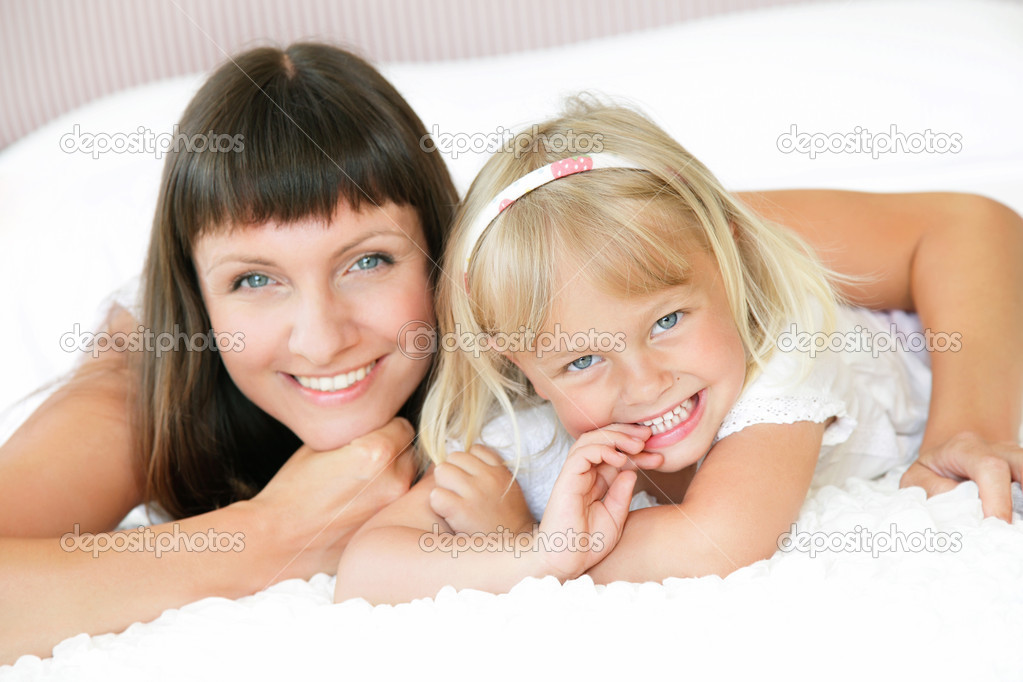 Mother and daughter posing happily in bed. Shallow DoF. Focus on daughter.