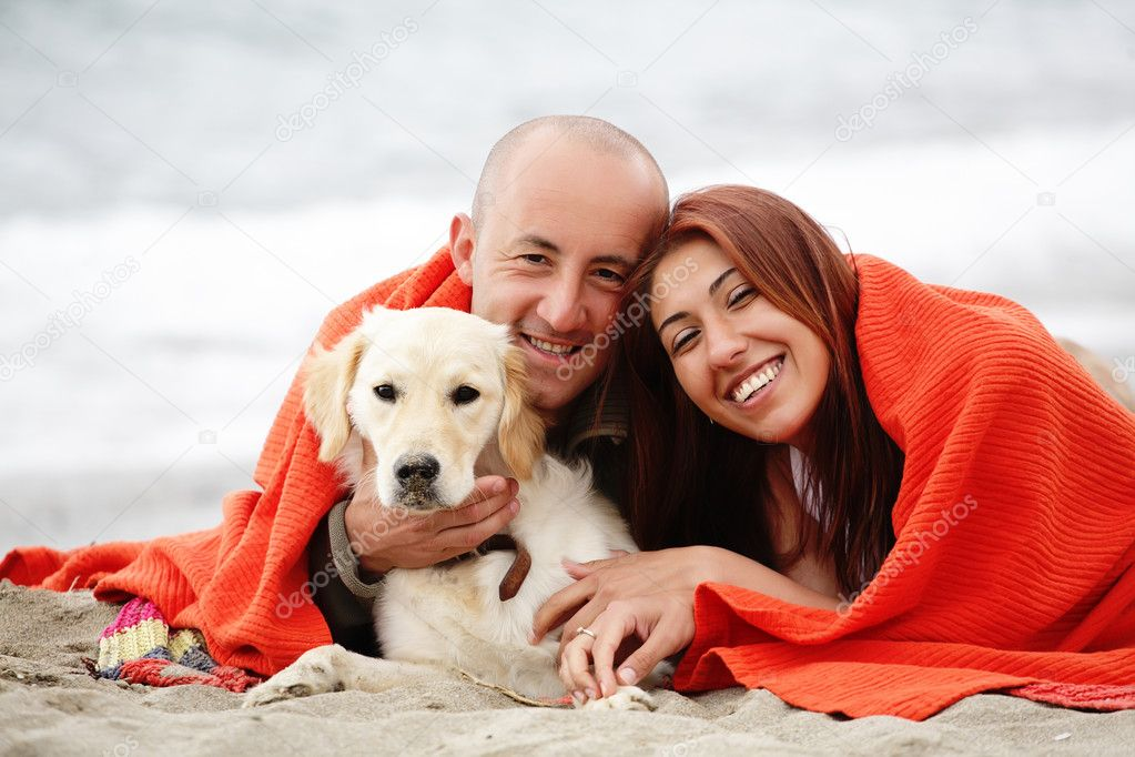 Romantic couple with a dog having fun on the beach