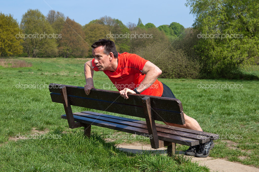 Man exercising doing pressups on a Park Bench in the Sun