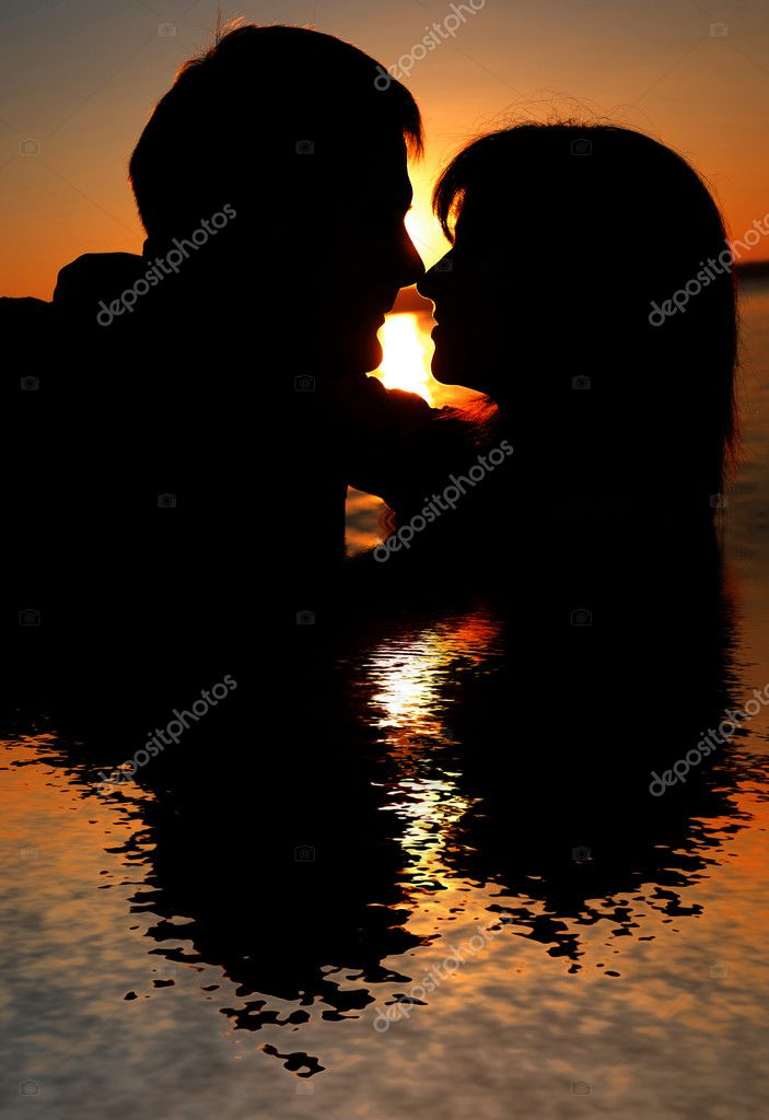 Reflexion of couple kissing at sunset