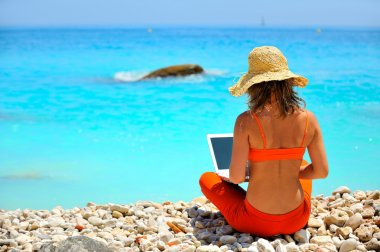 Young woman using laptop on the beach stock vector