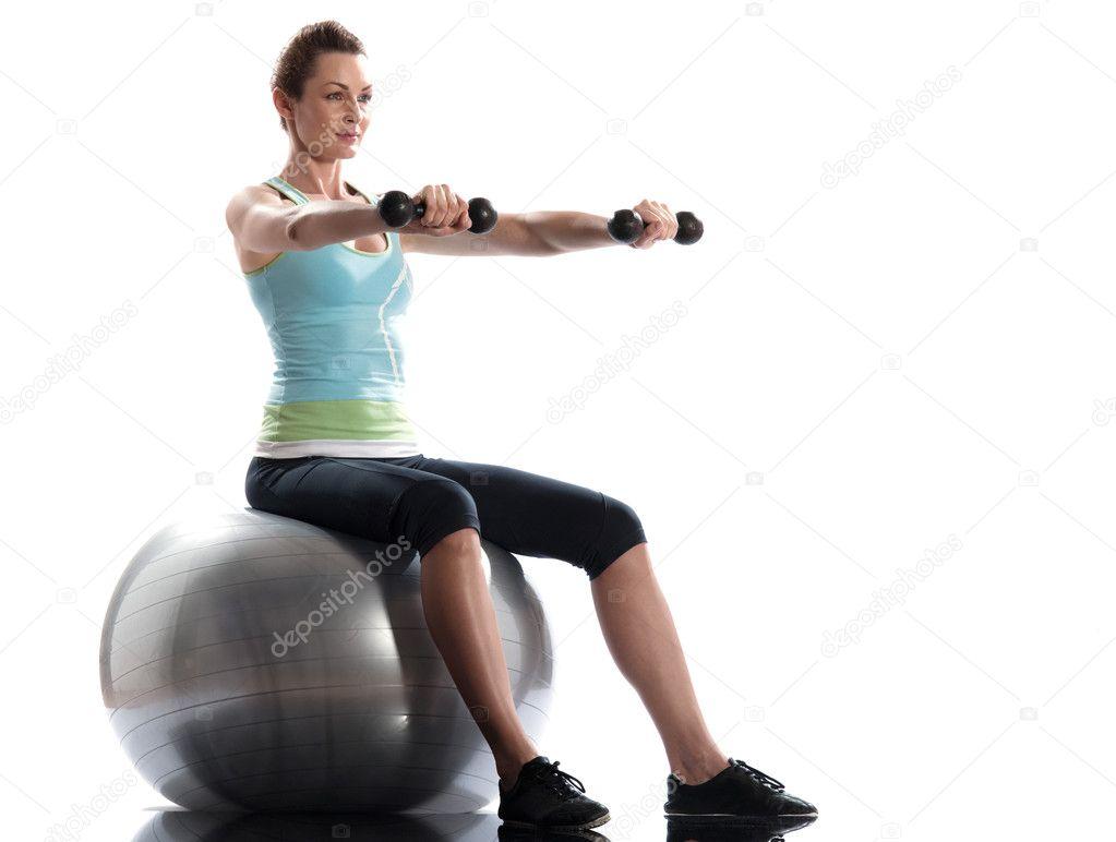 Una mujer caucásica de ejercicio de entrenamiento de peso entrenamiento  sentado en acondicionamiento físico suizo bola longitud total aislado sobre  fondo ... 8112298da3cd
