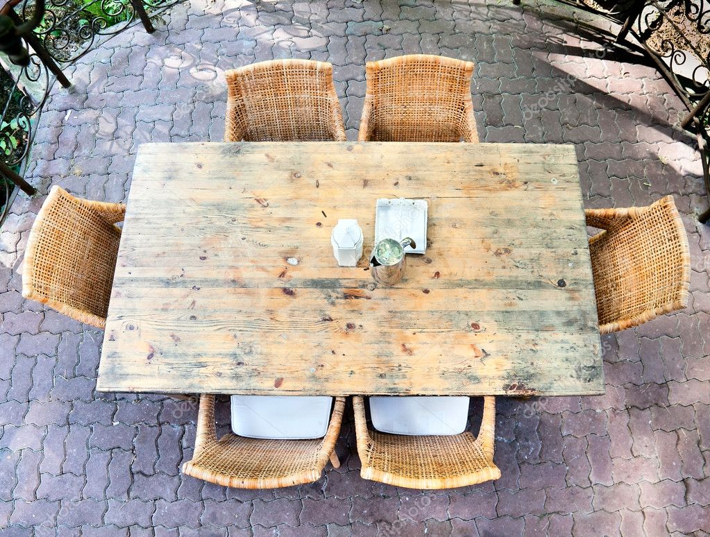 Dining wooden table with wicker chairs