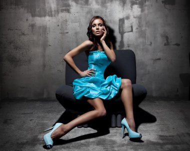Stunning brunette sitting and posing on a chair in fashion dress