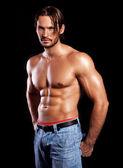 leistungsstarke muskulösen Mann isoliert auf schwarz