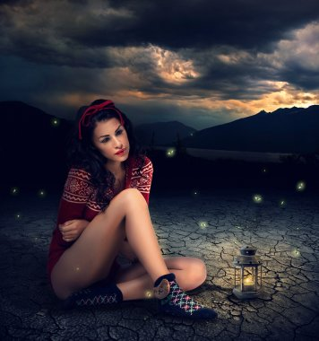 Fantasy style photo of a young beauty brunette woman with Candle Lamp