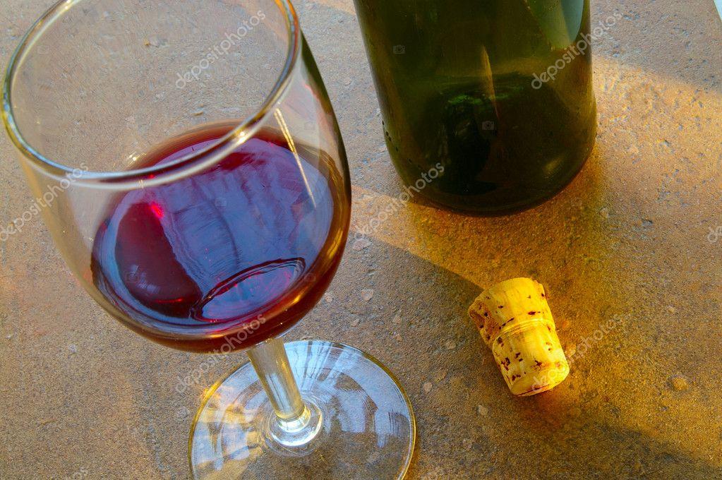 Bicchiere di vino e sughero sulla superficie della piastrella
