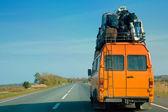 Malý autobus s taškami na střeše