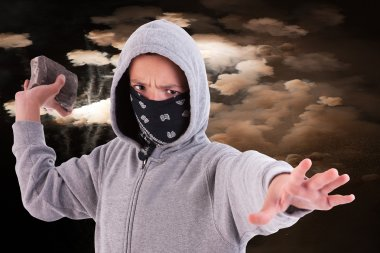 A teen with a rock, in a act of juvenile delinquency, with clouds of smoke background