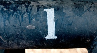 The number 1 on rusted old iron surface