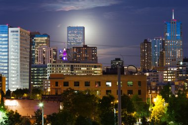 Glowing Full Moon Rises Behind The Denver Colorado Skyline