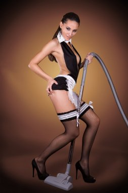 Beautiful woman dressed in a sexy French Maid costume vacuum cleaner