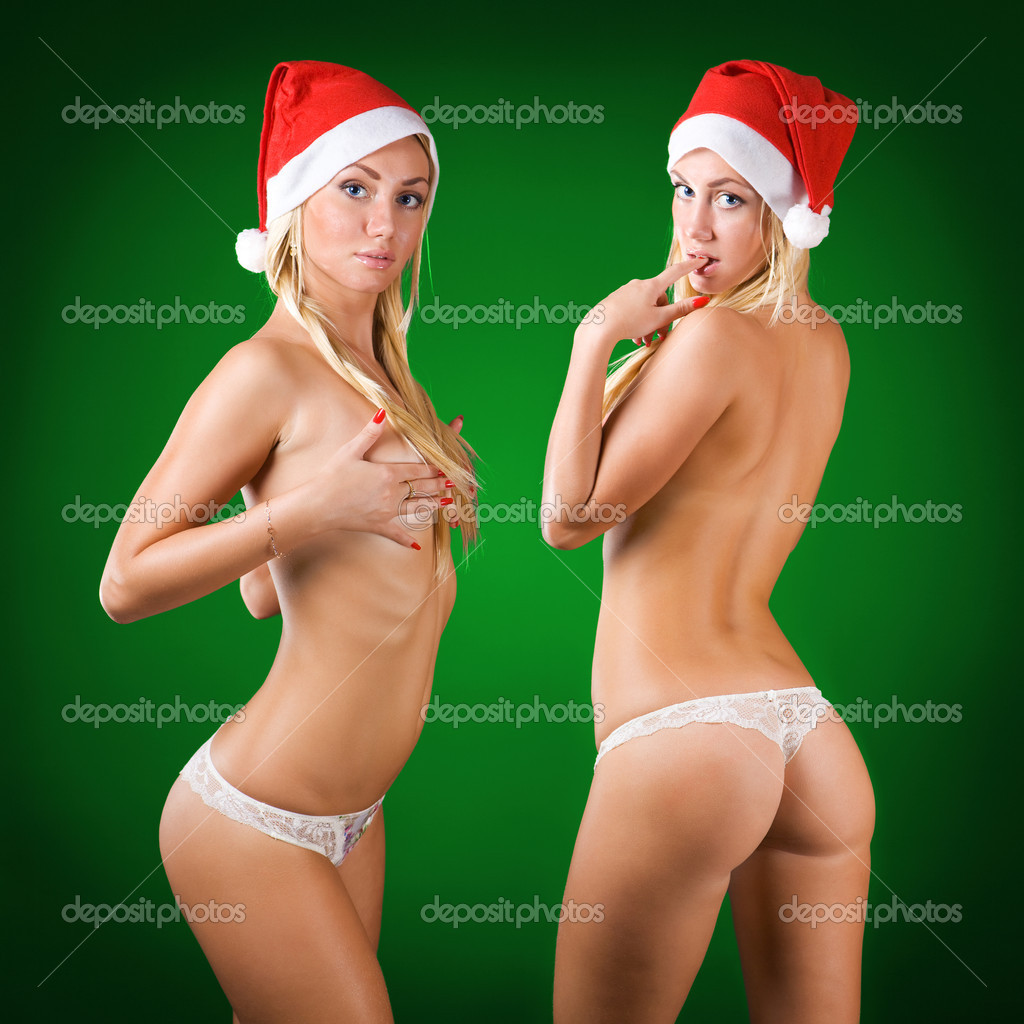Two cute sexy topless blond girls wearing santa claus cap green background