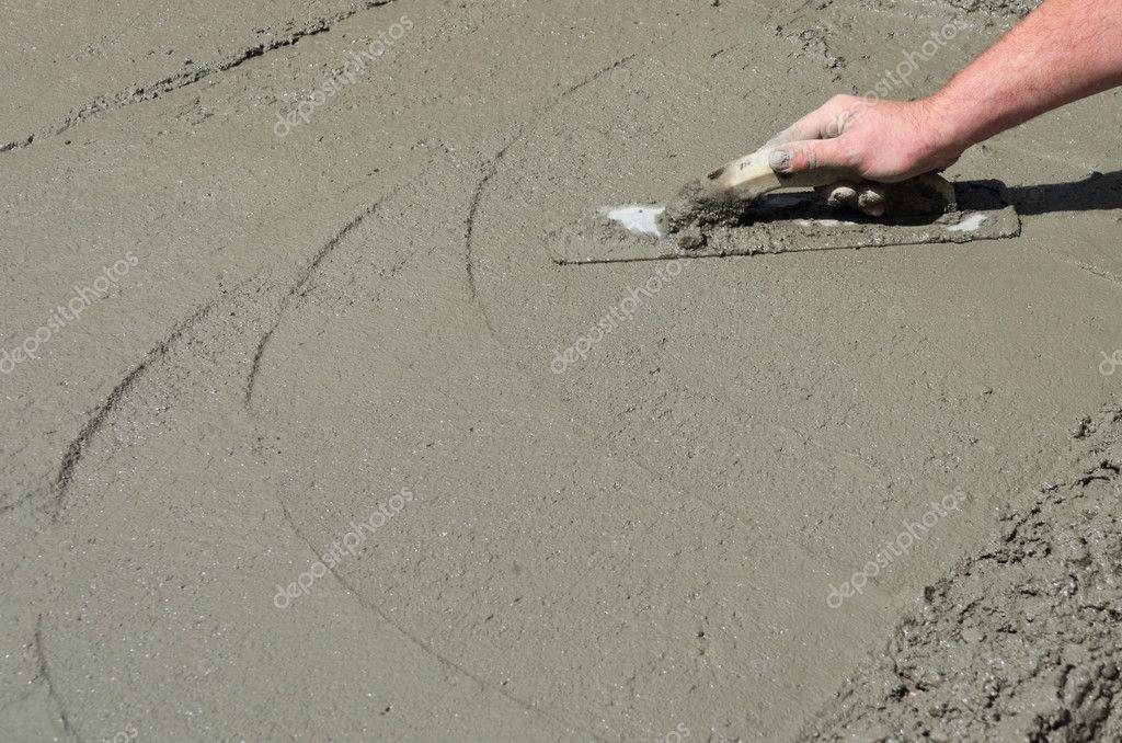 Contractor hand finishing concrete floor