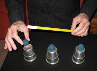 Magician with three balls and cups