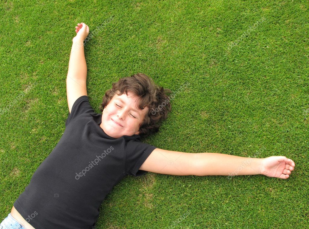 Happy child resting on grass