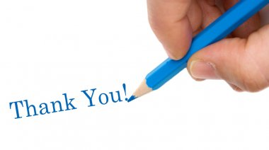 Hand with blue pen writing Thank You