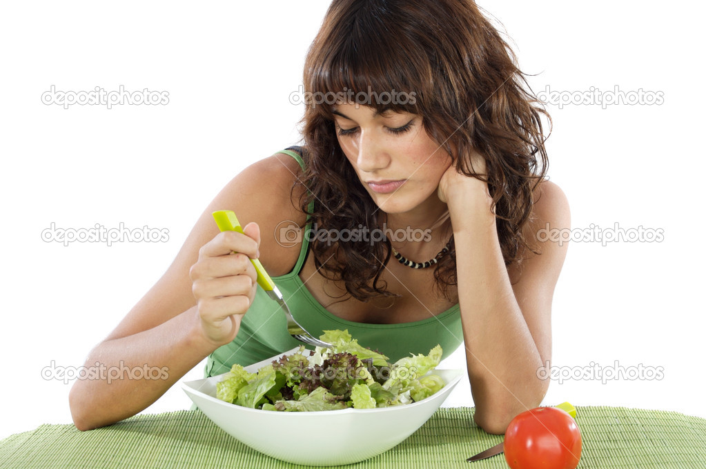 A sad teen eating salad. Care his diet.