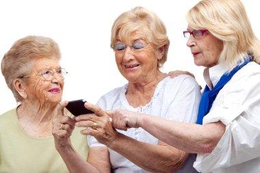 Three elderly women with cellphone.