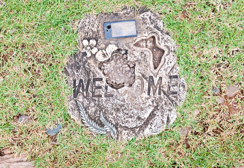 Broken welcome stone on green grass background