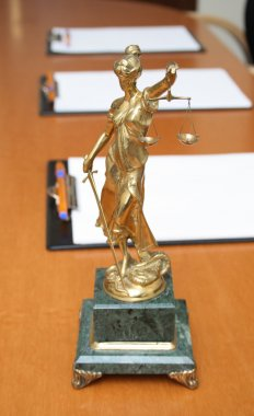 Scales of justice and blank paper on a table