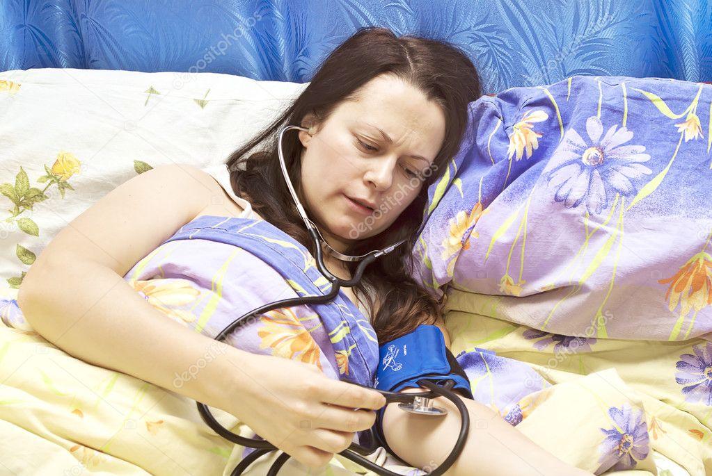Das Mädchen im Bett misst den Druck — Stockfoto © m