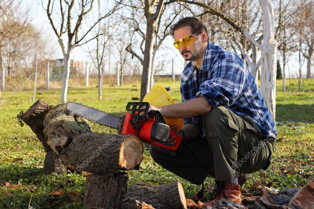 Man cutting wood with electric saw