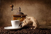 Horizontal view of an espresso cup surrounded by cofee beans and
