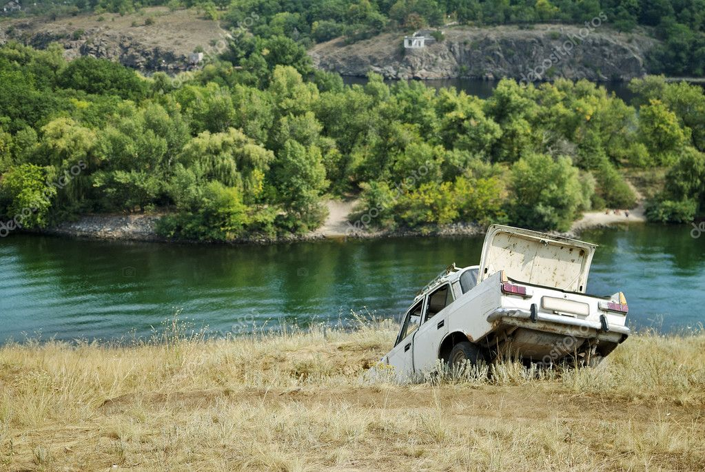 Abandoned car on the riverbank near the water