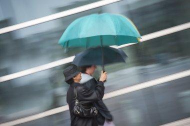 Two women under umbrella in rain