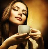 Fényképek kávét iszik, a gyönyörű nő