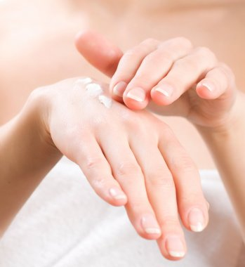 Female applying moisturizer to her Hands after bath