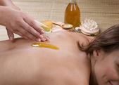 lázně. mladá žena dostat masáž. nalévání masážní olej