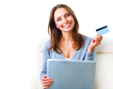 Smiling Woman shopping online with credit card and computer.Inte