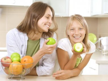 Happy Family Mother with her Daughter eating Healthy food. Diet.