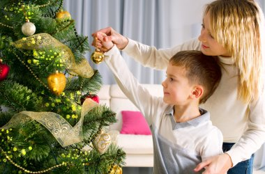Kids decorating a Christmas tree with baubles in the living-room
