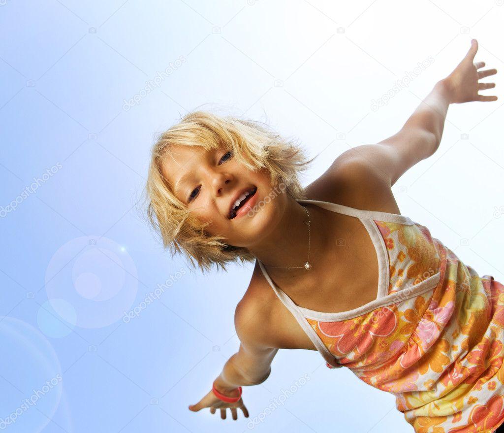 Happy Cute Little Girl Having Fun. Over Blue Sky