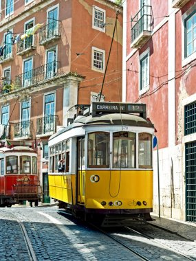 Traditional yellow and red trams downtown Lisbon. Trams are used