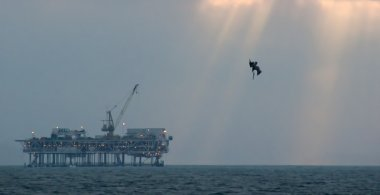 Off Shore Oil Platform with Pelican Diving in Ocean