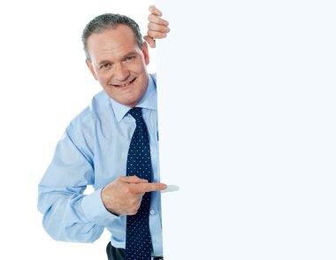 Businessman peeking behind a whiteboard